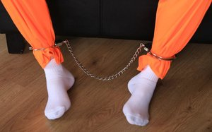 Female prisoner is left alone while cuffed in an orange jumper and white socks