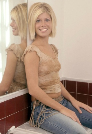 Natural blonde wets her nice ass in the bathroom after taking off blue jeans