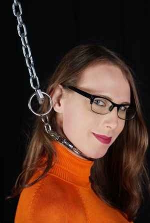 Clothed female watches time pass by on her watch while cuffed and chained 80154997