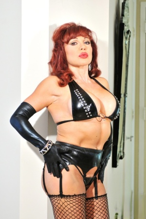 Latina redhead Sexy Vanessa sits on a dildo stand in latex fetish wear