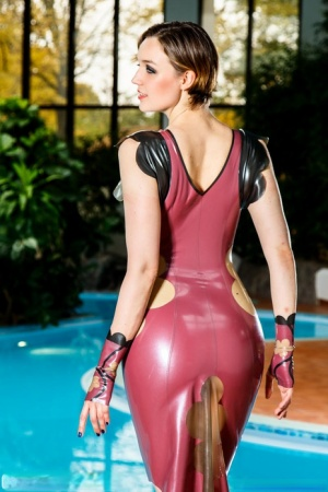 Solo model poses non nude in a knee-length latex dress by indoor pool