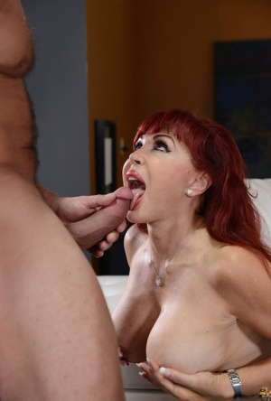 Latina redhead Sexy Vanessa holds her big tits during a blowjob on her knees