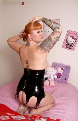 Tatted redhead Mette models a latex corset while showing her big ass and twat