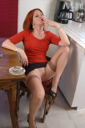 Redhead female Mina smokes while showing her pussy in tan stockings 95679353