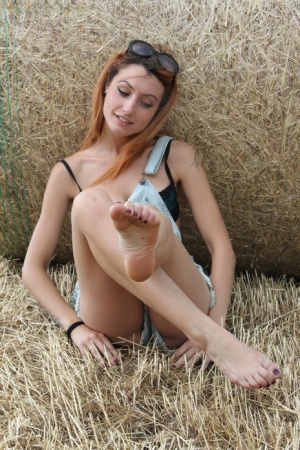 Inked redhead Thena puts her bare feet on display next to a round bale of hay