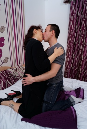 Mature redhead partakes in foreplay with her toy boy while losing her clothing