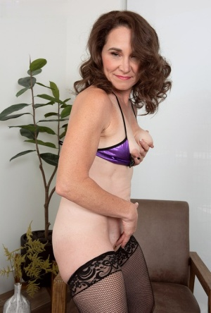 Middle aged lady Carrie Anne cups her tiny tits while standing nude in hosiery