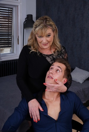 Older blonde takes a cumshot on her big boobs after sex with a younger boy