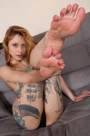 Tattooed redhead Stella shows the bottoms of her feet while getting naked