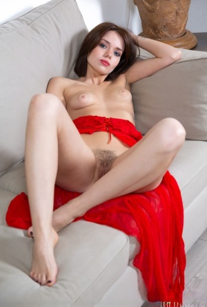 Young model with striking eyes removes red negligee to pose nude