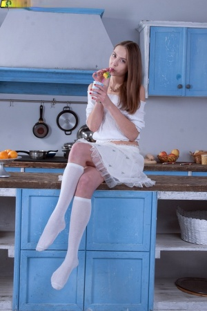 Sweet girl Valery exposes her tiny tits in white knee socks and a thong