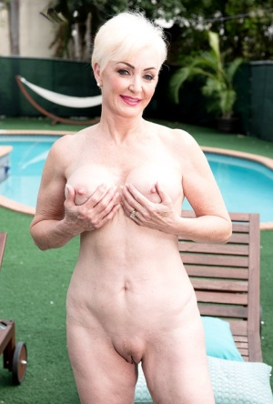 Older blonde Seka Black poses in the nude while enjoying a glass of wine