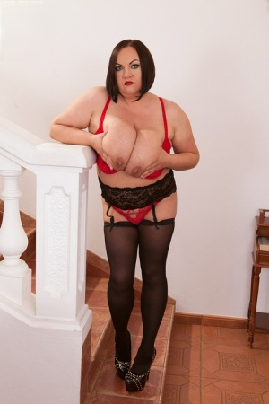 Solo model Natascha Romanova frees her massive tits from a red dress