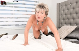 Mature lady Constance Joy gets naked in a bedroom in OTK suede boots