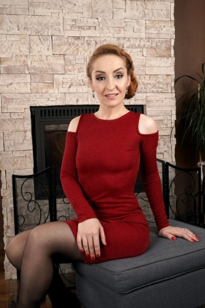 Over 30 redhead Di Devi removes a red dress while stripping to her stockings