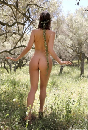 Brunette beauty sports the hippie look while totally naked in an orchard