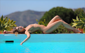 Solo girl with a tight ass and perky tits poses nude on the side of a pool