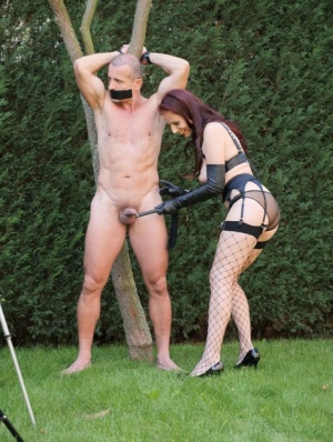 Dominant girl Mistress Antonia tortures a naked man while hes tied to a tree