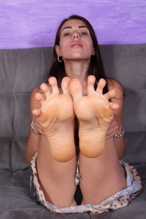Solo girl Petra curls and uncurls her toes while wearing a dress