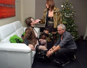 Mature amateurs share a lesbian kiss in front of a man at Christmas