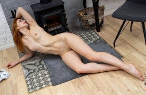 Redheaded girl Siiri gets completely naked in front of a wood stove