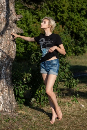 Skinny blonde Azshara strips bare naked in front of a mature tree