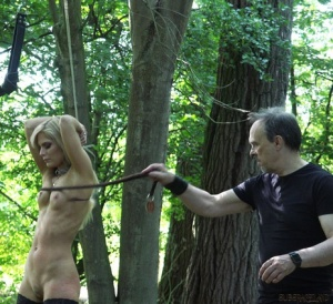 Restrained blonde Candee Licious is paddled and whipped in a forest 83557646