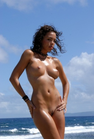 Solo model Corail removes a swimsuit to pose naked on an oceanside cliff