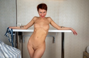 Older lady with short red hair strikes confident nude poses in black heels