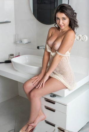 Young brunette Dionisia highlights her tight slit while naked in a bathroom