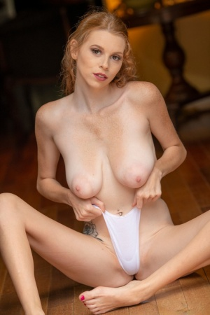 Sexy redhead Rhia Lynn uncovers her big boobs before sitting naked on a floor