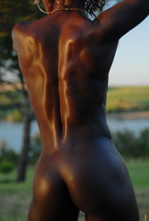 Dark chocolate skinned female shows the pink of her twat during closeup action