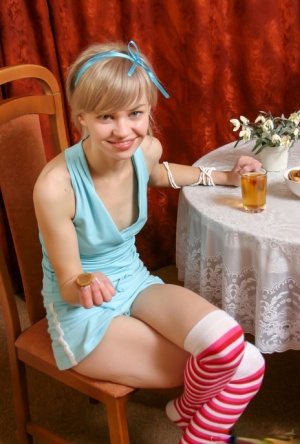 Adorable teen Cindy B gets naked on a dining room chair in striped OTK socks
