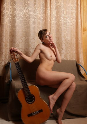 Sweet redhead Lana Y strums an acoustic guitar before getting butt naked