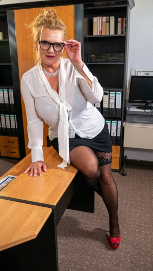 Busty mature secretary masturbates while at work on her chair