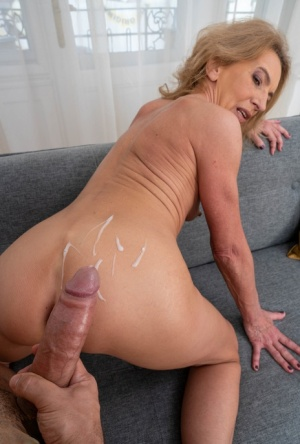 Old blonde woman takes a cumshot on her ass after after sex with her toy boy