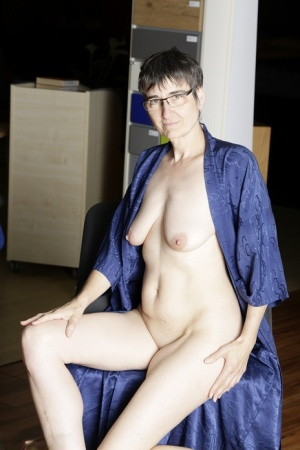 Mature amateur admires her naked body in a mirror while wearing black heels