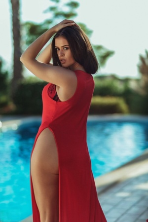 Beautiful brunette Brook Wright removes a long gown to model naked by a pool