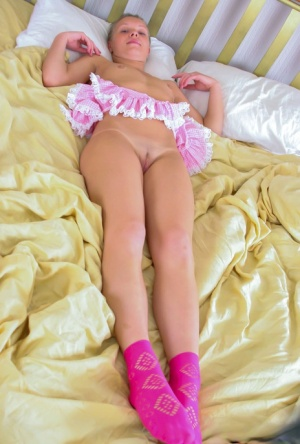 Young looking girl Bella D shows her bare ass and slit on a bed in pink socks