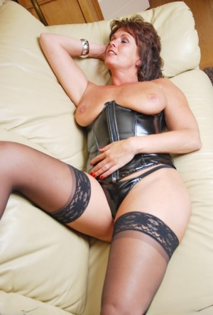 Hot older woman removes a corset and thong to pose nude in stockings