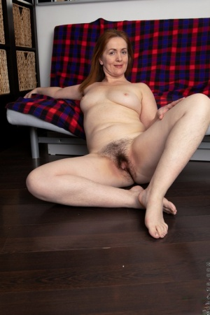 Mature redhead Gloria highlights her trimmed pussy during her first nude gig