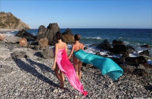 Beautiful lesbians model for a glamour shoot during a seaside shoot