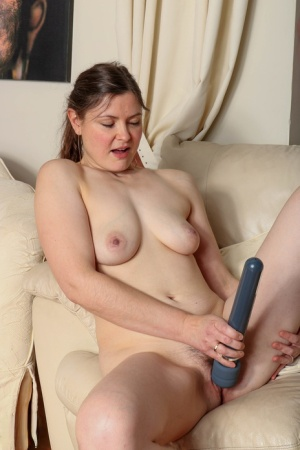 Happy homemaker masturbates on a couch during her first nude poses