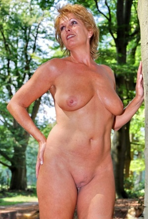 Mature redhead Luscious Models displays her great body while in a forest 18551226