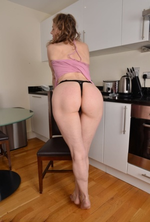 30 plus female Alexia S removes a dress and lingerie to get naked in a kitchen
