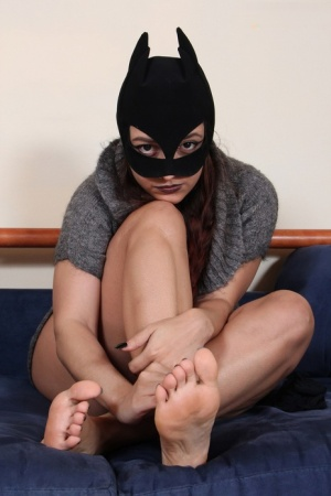 Clothed female Ladynight sports a mask while taking off her boots and socks