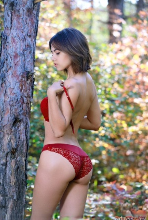 Young beauty Dzhili highlights her tight ass getting naked by the woods