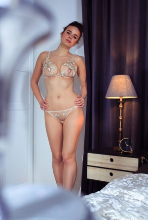 Young brunette Arcadia removes a bra and thong set to model bare naked