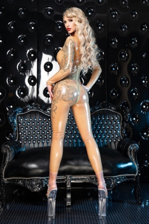 Gorgeous blonde models a latex catsuit in over-the-top platform heels