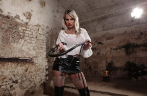 Hot blonde wields a bull whip while freeing her hose clad feet from long boots
